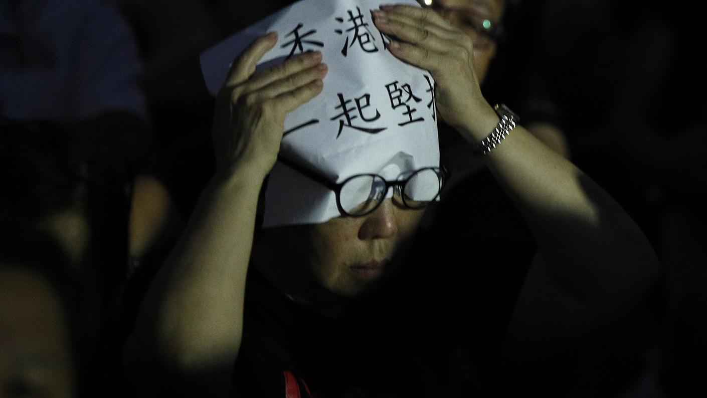 """一名香港民众在头上放着""""香港 一起坚持""""的标语。(美联社)"""