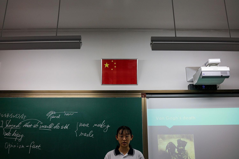 资料图片:2017年9月28日,一名学生站在上海学校教室的中国国旗下面。(法新社)