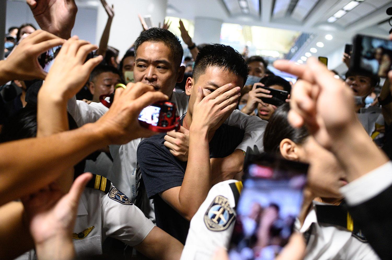 2019年8月13日,一名被怀疑是中国公安的男子(中)在香港国际机场被包围。(法新社)