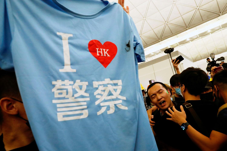 """2019年8月13日,在中国香港国际机场示威活动中,《环球时报》记者付国豪(C)的一件T恤,上面写着""""我爱香港警察""""。 (路透社)"""