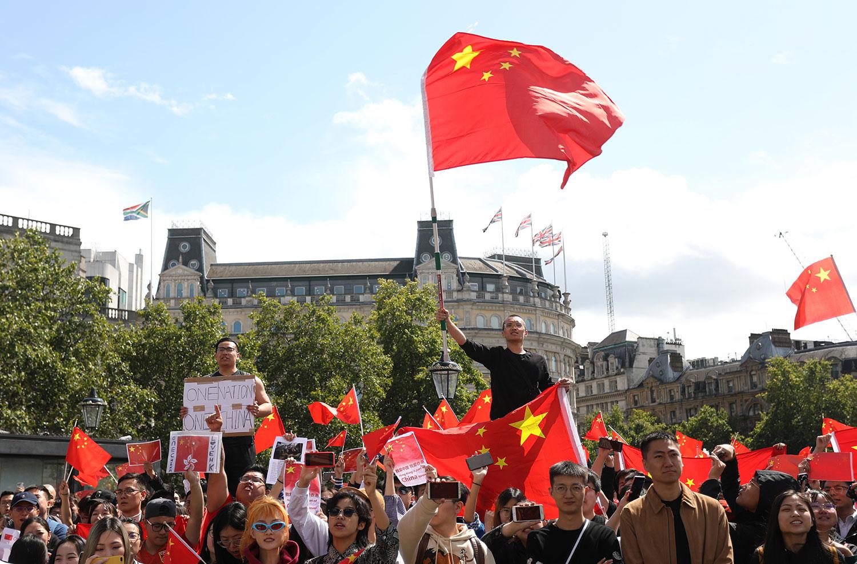 2019年8月17日,一批来自中国大陆的留学生在英国伦敦举行集会,他们唱出这首经典儿歌,寓意香港只有背靠中国大陆,才有未来。(法新社)