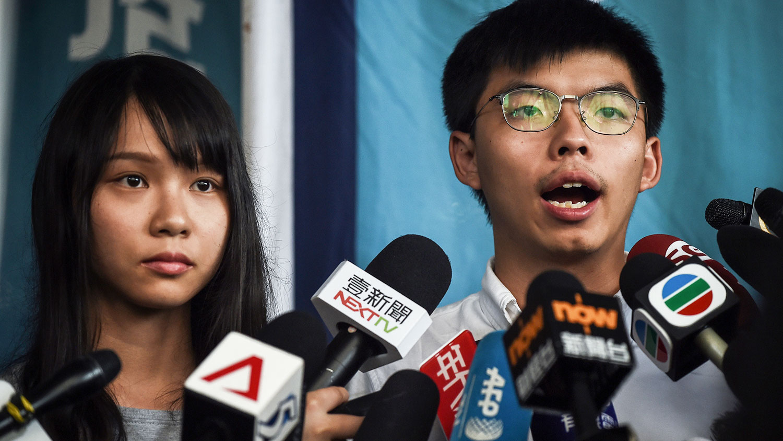 2019年8月30日,目前黄之锋和周庭暂获准保释,案件于11月8日再提堂。图为香港众志秘书长黄之锋(右)和成员周庭(左)在香港地方法院外向媒体发表讲话。(法新社)