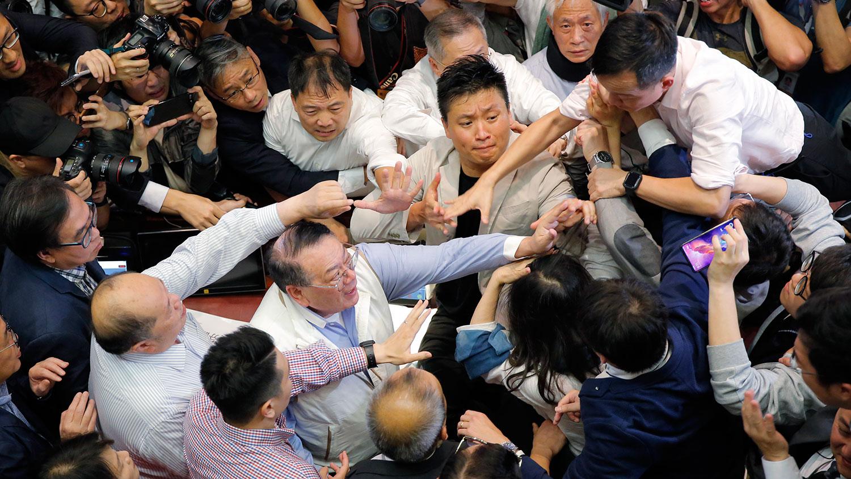 """2019年5月11日,《逃犯条例》修订草案的争议在香港不断升级,民主和建制两派议员在立法会""""争夺阵地""""的过程中发生推撞,导致数名议员受伤。 (美联社)"""