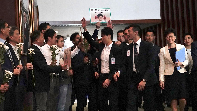 2019年10月17日,香港特首林郑月娥抵达香港立法会会议厅,民主派议员抗议。(美联社)