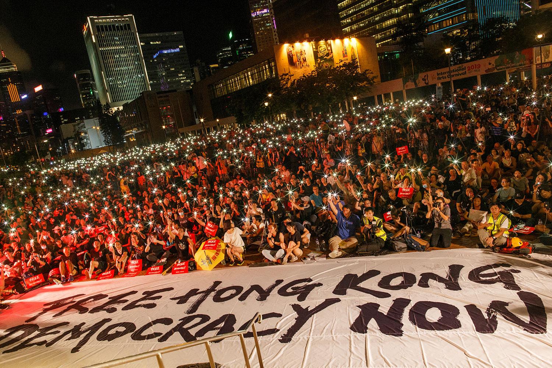 2019年6月26日晚上,20国集团峰会前,示威者在集会期间挥动智能手机,要求政府回应撤回《逃犯條例》修订等诉求,并希望趁二十国集团蜂虎即将揭幕,寻求国际社会关注香港人的声音。(路透社)