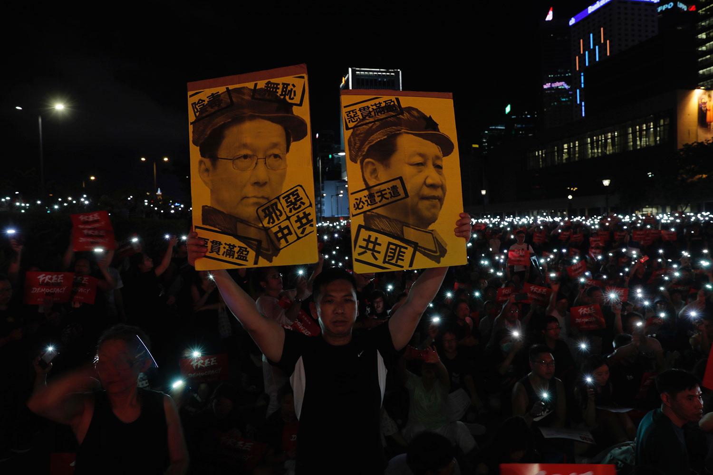 """2019年6月26日,在香港集会上抗议者手持标牌""""习近平与韩正画像""""。(美联社)"""