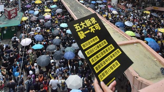 """资料图片:2019年7月21日香港反送中大游行,市民手持标语牌:""""五大诉求 缺一不可""""。(图源:维基百科)"""