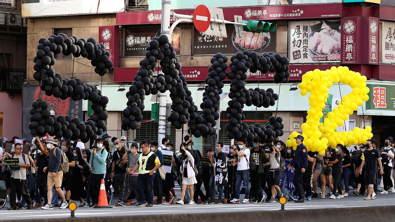 资料图片:2020 年 10 月 25 日,台湾台北民众游行,要求释放被大陆抓获的12名逃离香港的抗议者。 (美联社)