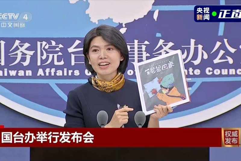 国台办发言人朱凤莲手持一本童书《等爸爸回家》。(截自央视)