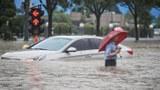 2021 年 7 月 20 日,河南省郑州市,一名男子沿着被洪水淹没的街道,旁边趟过一辆被淹没的汽车。