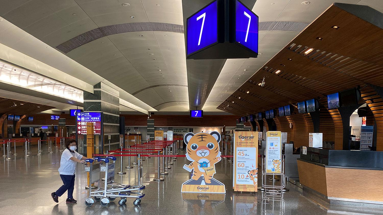 一名员工戴着口罩,将手推车推过台湾台北桃园国际机场的空柜台。(路透社图片)