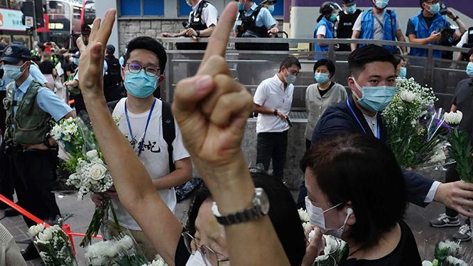 """2020年8月31日,一名民众在香港地铁太子站外打出了""""五大诉求缺一不可""""的手势。(美联社)"""