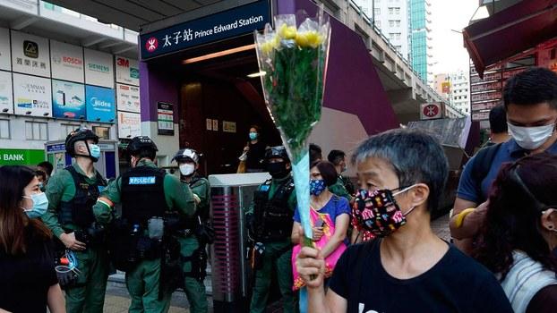 今年8月31日是香港831太子站事件一周年。图为当天地铁太子站外手捧鲜花纪念的一名妇女。(美联社)