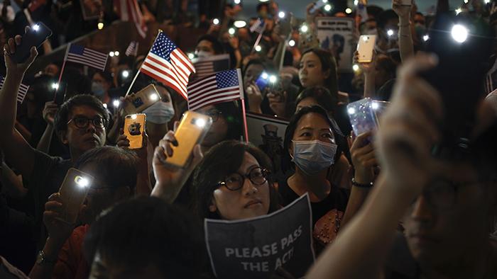 香港民众2019年10月14日上街抗议,其中有人举牌要求美国通过《香港人权民主法案》。(美联社)