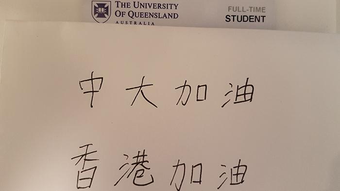 """澳大利亚昆士兰大学网友展示出所属学校的证件,并附上写有""""中大加油、香港加油""""等字句。(品葱网)"""