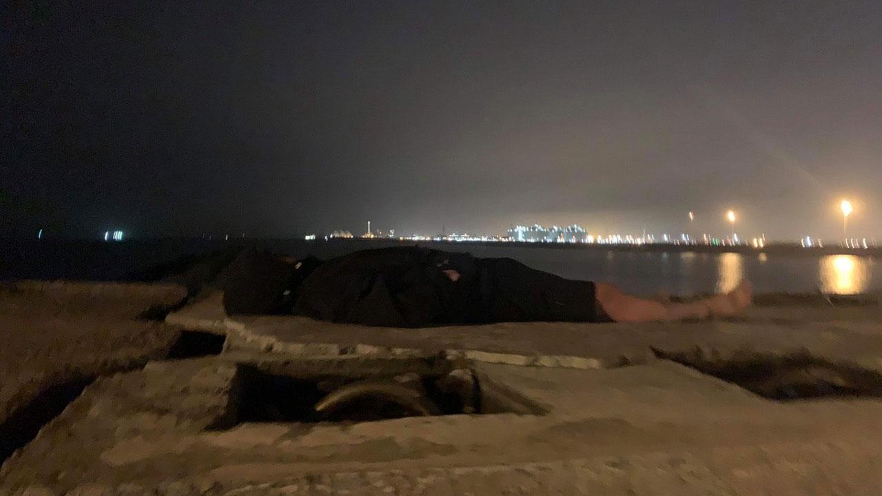 周男吃了台湾挖土机工人给的便当后就在堤防呼呼大睡。(民众林学贤提供)