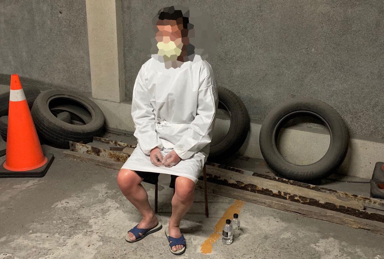 防疫期间,港警给周男穿上全身防护衣并量体温。(翻摄侦办资料)