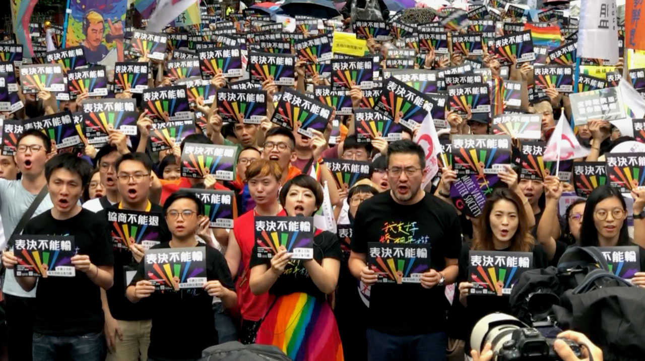 支持同性婚姻者从淋雨在场外守候。(记者夏小华摄)