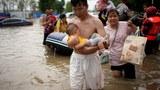 2021 年 7 月 22 日,中国河南省郑州市暴雨过后,一名抱着婴儿的男子在被洪水淹没的道路上跋涉。