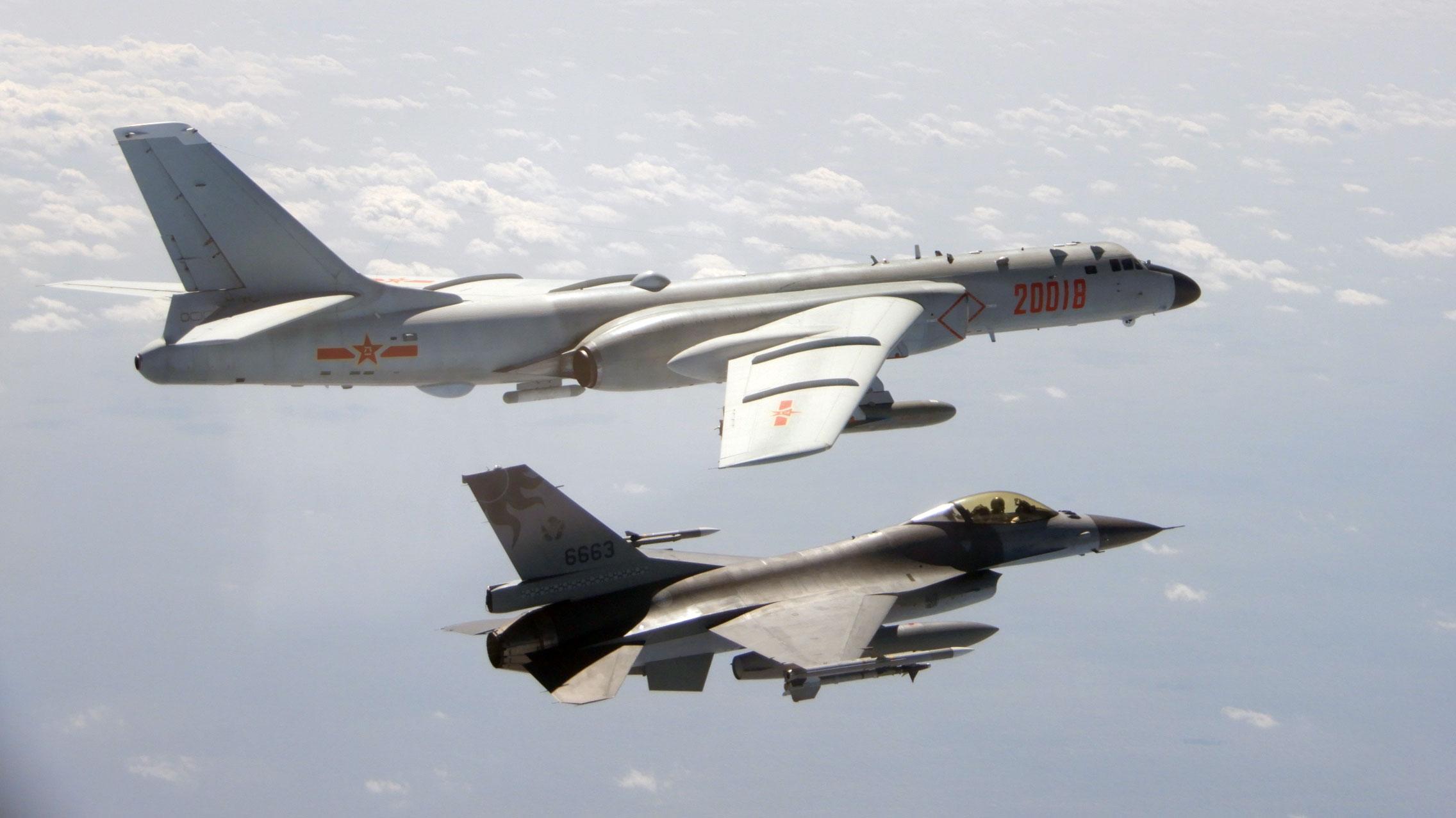 解放军轰6(左)等型军机10日再次执行远海长航训练,期间曾短暂逾越海峡中线,国军F-16(右)战机挂载实弹监控共军轰6。(国防部提供)