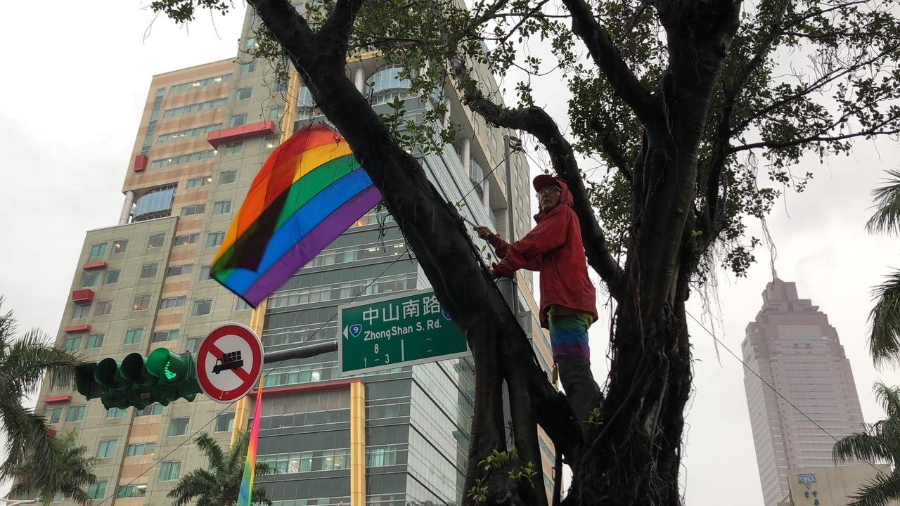 游行现场祁家威总会寻求制高点挥舞彩虹旗。(记者夏小华摄)