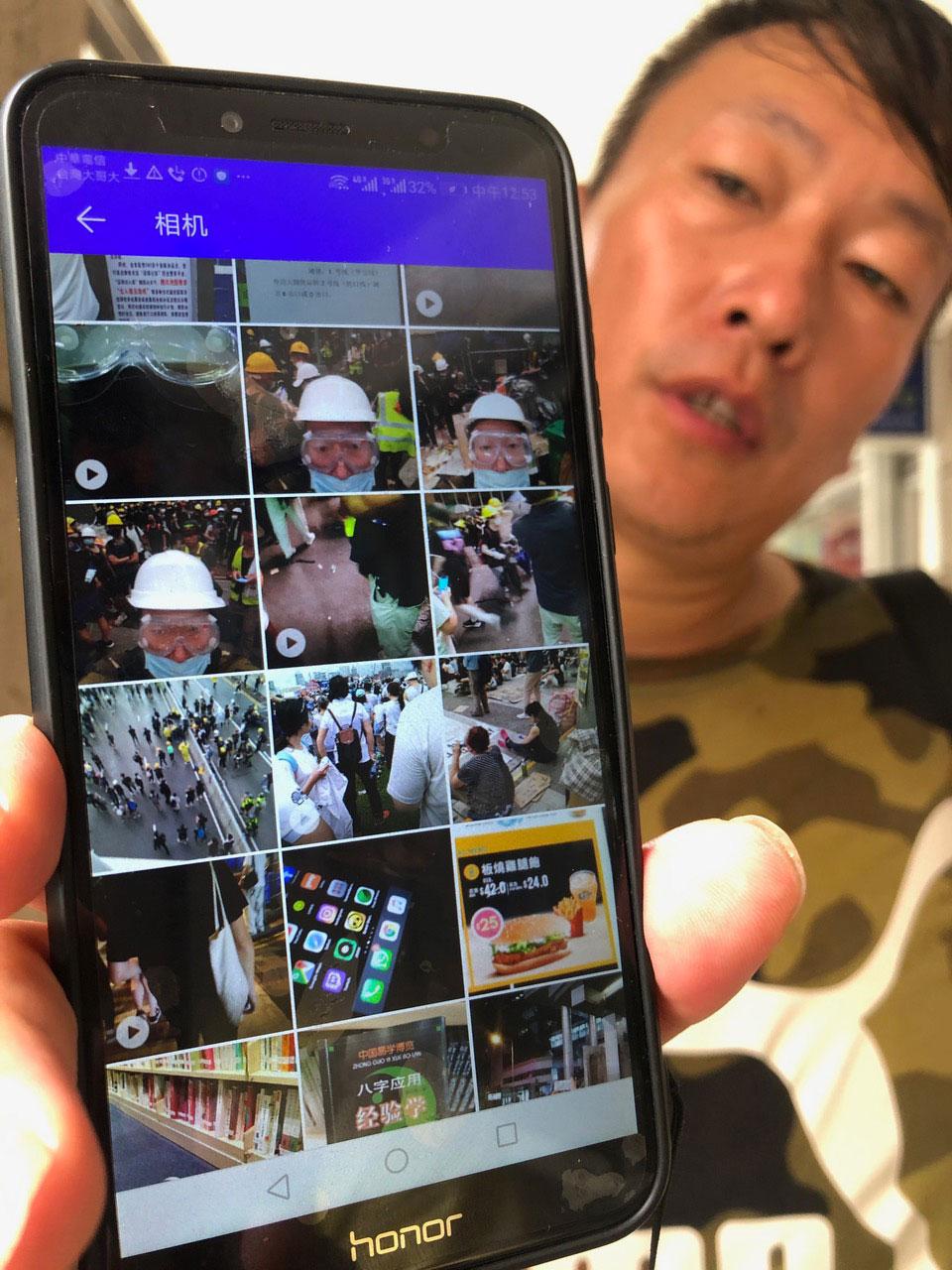 张文出示他手机里存有部份参与香港反送中的照片和视频。(记者夏小华摄)
