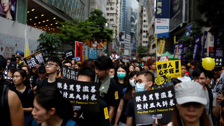 """019年8月18日, 香港反送中大游行,示威者举起:""""彻查黑警滥暴 坚持五大诉求""""等标语。(路透社)"""
