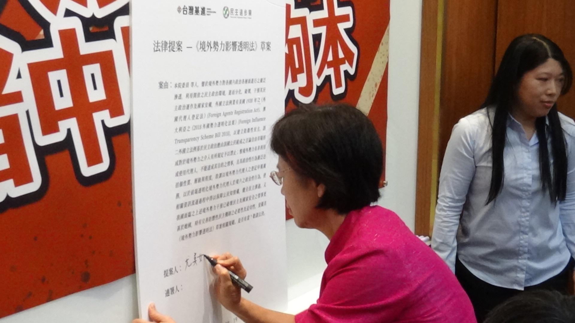 民进党立委尤美女签名连署基进党提出的《境外势力影响透明法》草案。(记者夏小华摄)