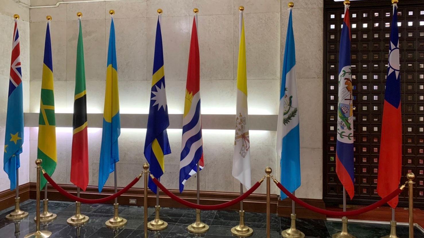 事发突然,外交部宣布和基里巴斯断交记者会后,仍可见基里巴斯国旗(右五、箭头指处)还在大厅未撤。(记者黄春梅摄)