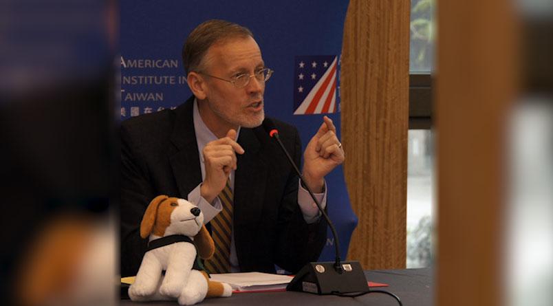 美国在台协会处长郦英杰22日在台北发表第四场政策性演说。他拿出米格鲁布偶说,在台湾机场看到这只米格鲁布偶,是从美国来的,台美正共同对抗非洲猪瘟。(AIT脸书)