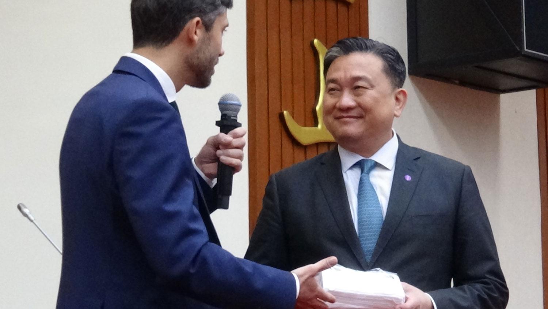 欧盟经贸协事处处长高哲夫(左)送上印有欧盟标志的口罩给立法院人权委员会会长王定宇。(记者夏小华摄)