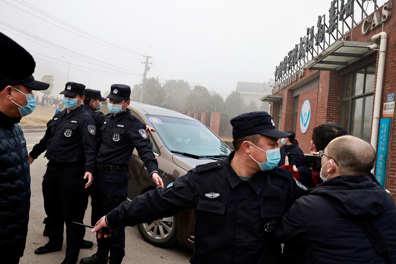 中国大陆警察阻挡前往调查新冠肺炎的世卫学者专家。(路透)