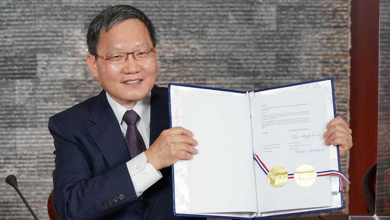 台湾财政部长苏建荣展示与中美洲银行视讯签署协定。(财政部提供)