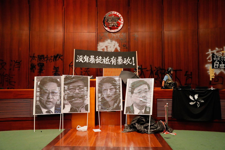 """2019年7月1日,逾百示威者一度占领立法会。图为7月2日立法会议厅摆放标语牌""""没有暴徒只有暴政!"""",和被污损的肖像。(美联社)"""