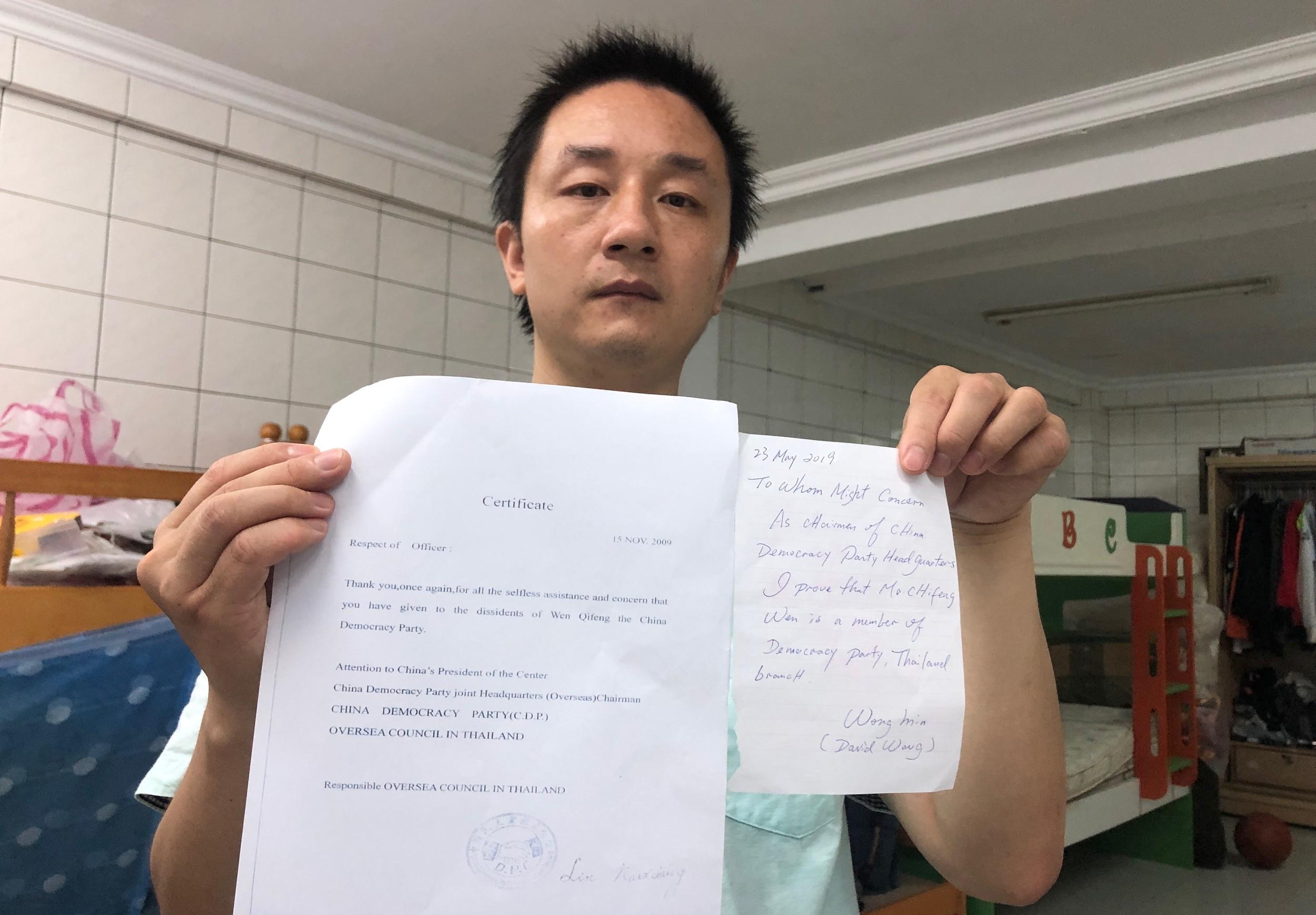 温起锋拿出两份中国民主党证明他是该党党员的文件,他说他左手这张是该党主席汪岷手签的文件,他希望对他取得身分更有利。(记者夏小华摄)