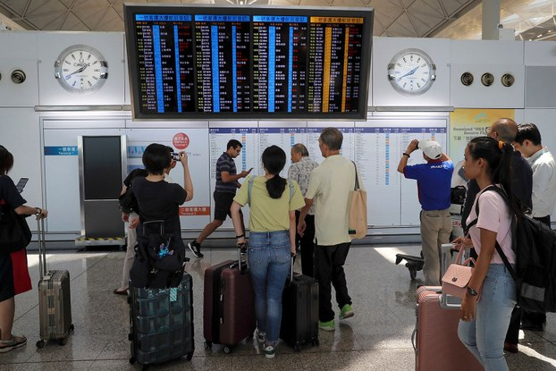 2019年8月5日, 在罢工阴霾下,香港国际机场离境大厅的电子广告牌上显示了一些航班被取消的信息。(美联社)