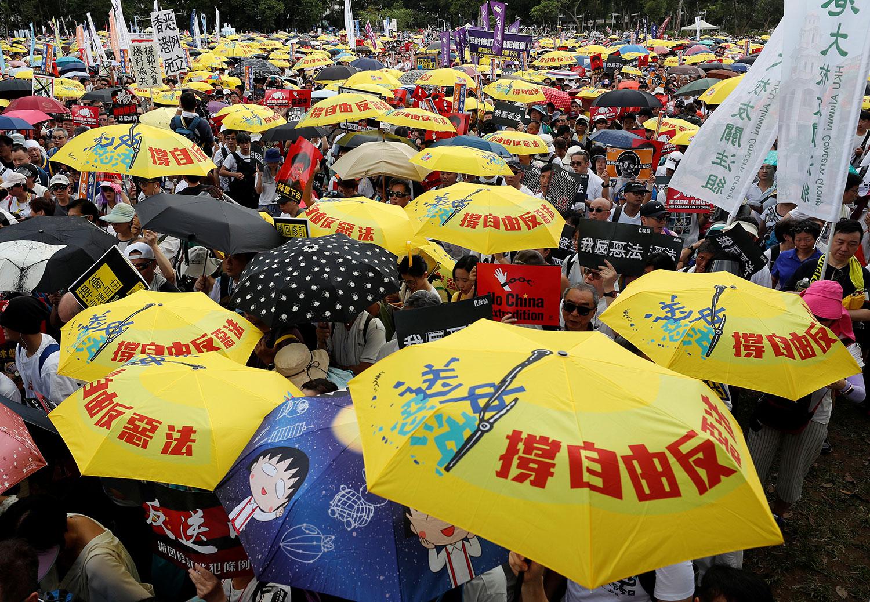 2019年6月9日,香港民间人权阵线举行反对修订《逃犯条例》的大游行,示威群众要求当局废除拟议中的把犯人引渡到中国的法案。示威者手持黄色遮阳伞,这是占领中环运动的象征。(路透社)