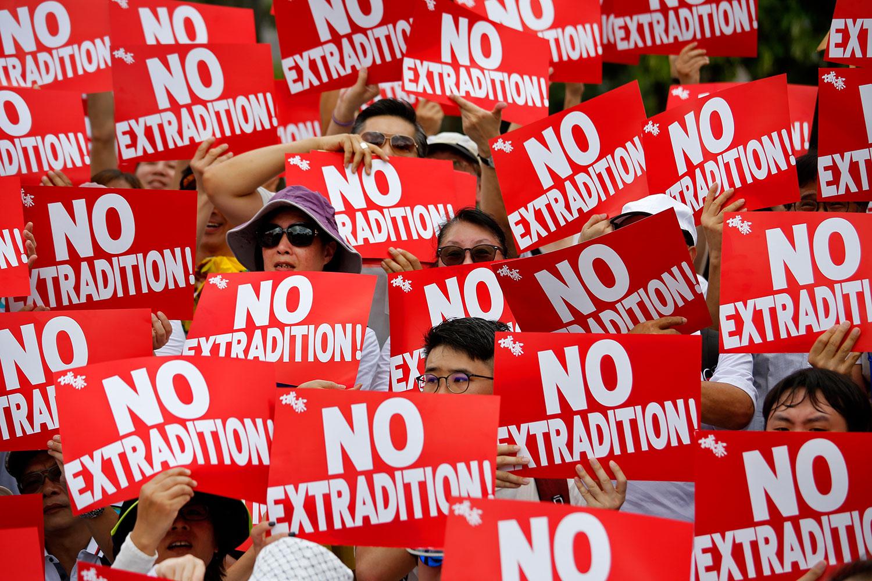 """2019年6月9日,香港民间人权阵线举行反对修订《逃犯条例》的大游行,示威群众手持着""""不要引渡""""口号。(美联社)"""