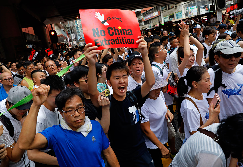 """2019年6月9日,香港民间人权阵线举行反对修订《逃犯条例》的大游行,示威群众手持着标语""""不要引渡到中国""""。(美联社)"""