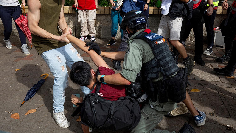 2020年7月1日,香港举行抗议国安法,一名防暴警察试图抓捕一名男子。(AFP)