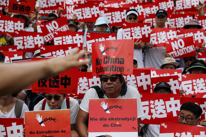 """2019年6月9日,香港民间人权阵线举行反对修订《逃犯条例》的大游行,示威群众手持着""""反送中""""等标号。(美联社)"""