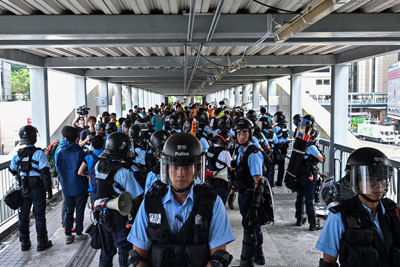 2019年6月13日,示威者在香港立法会外反《逃犯条例》,警察以暴力手段驱离示威民众后,警方在政府总部附近的天桥上守卫。(法新社)