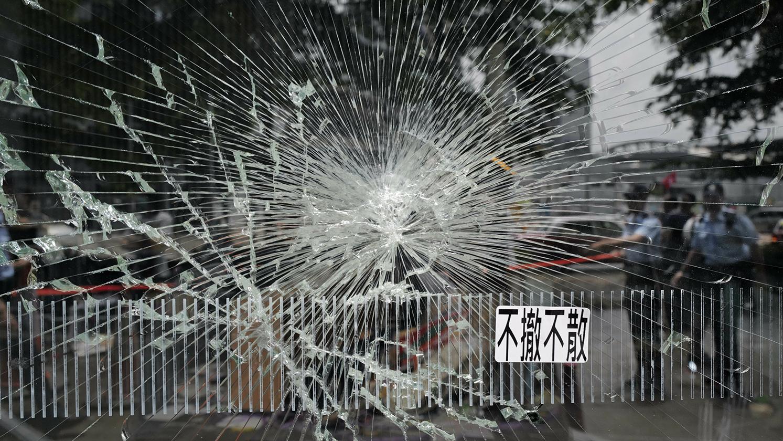 香港警方在香港立法会大楼一个破损的玻璃外执勤。(美联社)