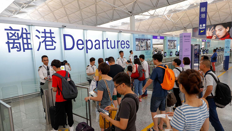 在中、港边境,中国海关近日大规模截查香港旅客,更强制翻查他们手机内的私资讯。图为2019年8月14日,旅客在香港机场登机口办理登机手续。(美联社)