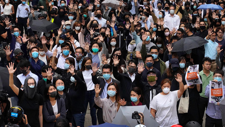 """2019年11月12日,香港办公室工作人员和亲民主示威者举起5只手指,代表""""五大诉求,缺一不可""""。(美联社)"""
