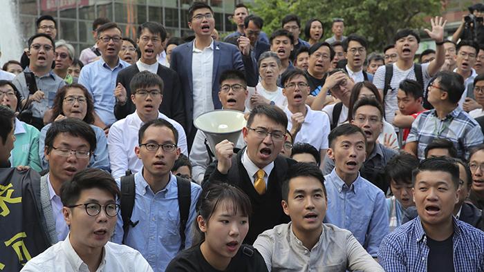 新当选的香港区议会部分民主派议员2019年11月25日聚集在香港理工大学附近(美联社)
