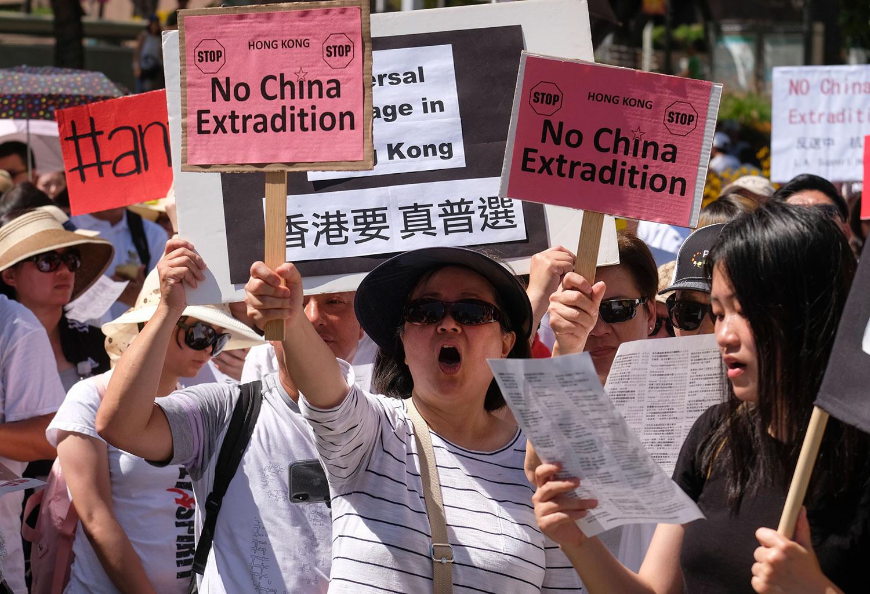 """2019年6月9日,香港百万人游行反对特区政府修订《逃犯条例》,示威群众手持着""""不要引渡""""和""""香港要真普选等""""口号。(法新社)"""