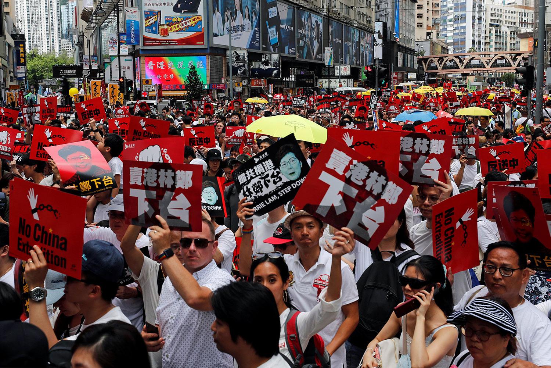 """2019年6月9日,香港百万人游行反对特区政府修订《逃犯条例》,示威群众手持着""""不要引渡""""和""""""""卖港林郑下台""""等口号。(路透社)"""