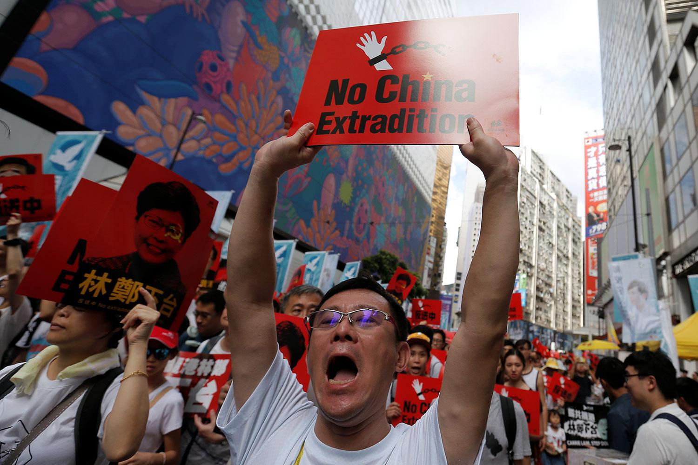"""2019年6月9日,香港百万人游行反对特区政府修订《逃犯条例》,示威群众手持着标语""""不要引渡到中国""""。(路透社)"""