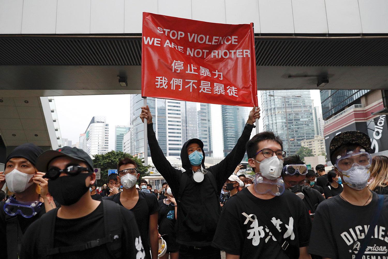 """资料图片:2019年6月17日,香港示威群众在立法会附近手持标语""""停止暴力 我们不是暴徒""""。(美联社)"""